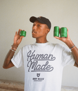 Pharrell Williams Holding His Skincare Products