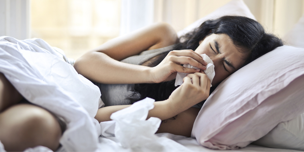 woman sneezing into tissues in bed