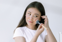 woman applying makeup on face